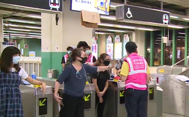 有戴口罩示威者站在入閘機前,容許市民免費入閘。(電視截圖)