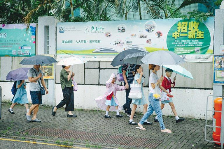 開學首日,家長在風雨中陪同子女上學。